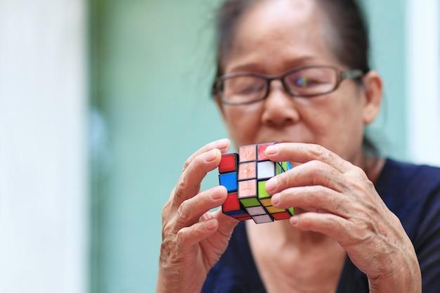 Asiatique femme senior jouer ou résoudre le jeu rubik cube. Photo Premium