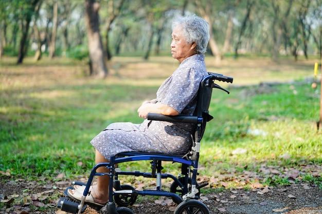 Asiatique femme senior patient sur une chaise roulante dans le parc. Photo Premium