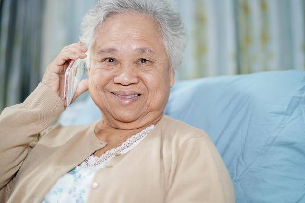 Asiatique femme senior patient parlant au téléphone mobile. Photo Premium