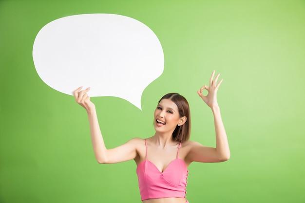 Asiatique femme tenant et levant à bulle de dialogue avec un espace vide pour texte sur vert Photo gratuit