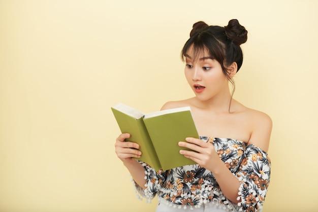 Asiatique femme tenant un livre ouvert et en regardant avec une expression d'incrédulité sur le visage Photo gratuit