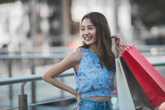 Asiatique femme tenant des sacs à provisions et levé les mains Photo Premium