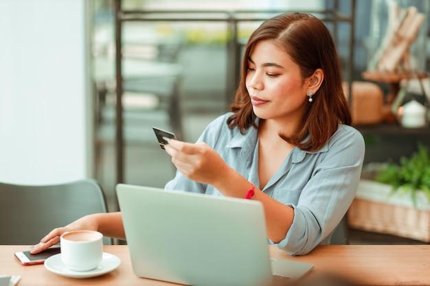Asiatique, femme, utilisation, téléphone portable, à, carte crédit, et, ordinateur portable, pour, achats, paiement en ligne, dans, café-restaurant Photo Premium