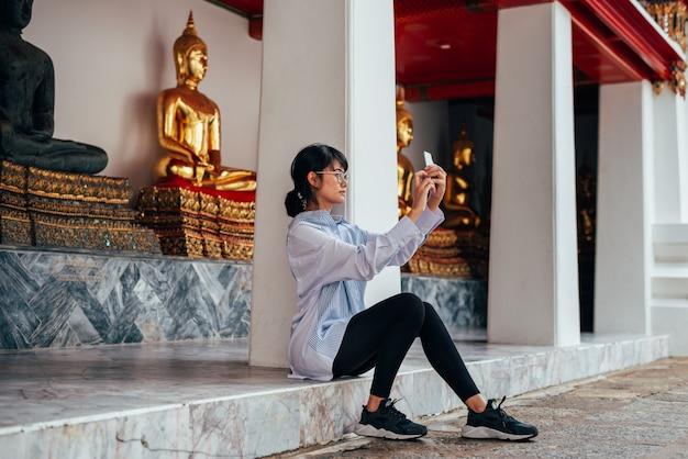 Asiatique femme voyageur s'asseoir et utiliser un smartphone selfie avec un fond de statue de bouddha Photo Premium