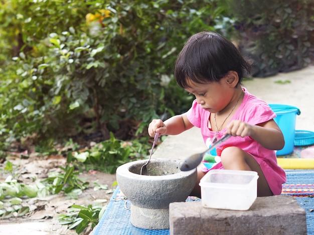 Asiatique Fille Joue à La Cuisine Avec Du Mortier Photo Premium
