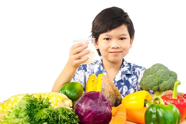 Asiatique garçon en bonne santé, montrant une expression heureuse avec un verre de lait et de variété de légumes frais Photo gratuit