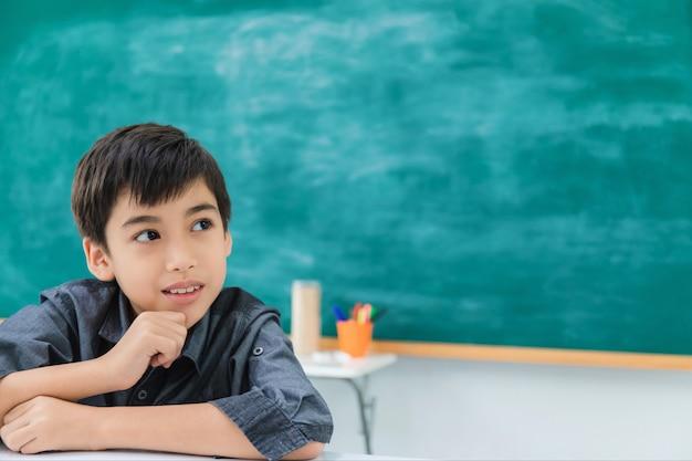Asiatique heureux écolier rêver et penser au tableau noir Photo Premium