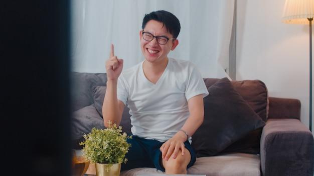 Asiatique homme d'âge moyen profiter de temps libre se détendre à la maison. les gars de style de vie heureux amusent regarder la télévision acclamant le sport de football et regarder des animations dans le salon dans la maison moderne la nuit Photo gratuit