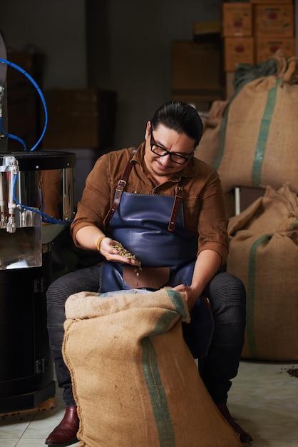 Asiatique homme d'âge mûr en tablier assis et vérifiant les grains de café du grand sac de jute Photo gratuit