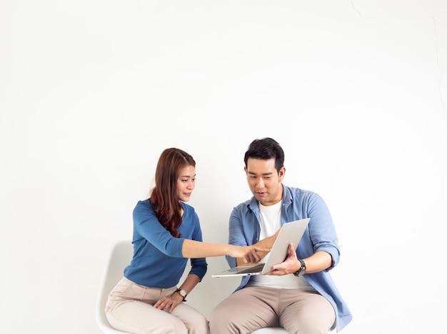 Asiatique homme et femme parlant avec un ordinateur portable pour entreprise sur fond blanc Photo Premium