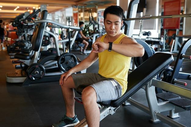 Asiatique, homme, séance, banc, gymnase, regarder, montre-bracelet Photo gratuit