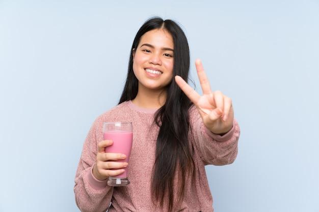 Asiatique jeune adolescente avec milkshake à la fraise souriant et montrant le signe de la victoire Photo Premium