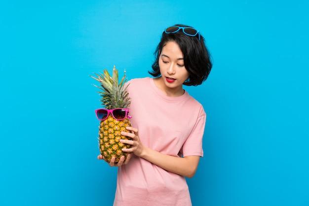 Asiatique jeune femme sur bleu isolé, tenant un ananas avec des lunettes de soleil Photo Premium