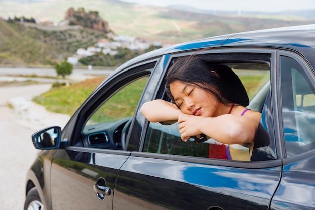 Asiatique, jeune femme, dormir, quoique, s'appuyer, fenêtre, de, voiture Photo gratuit
