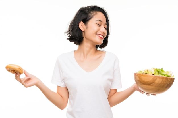 Asiatique jeune femme sur isolé avec salade et beignet Photo Premium