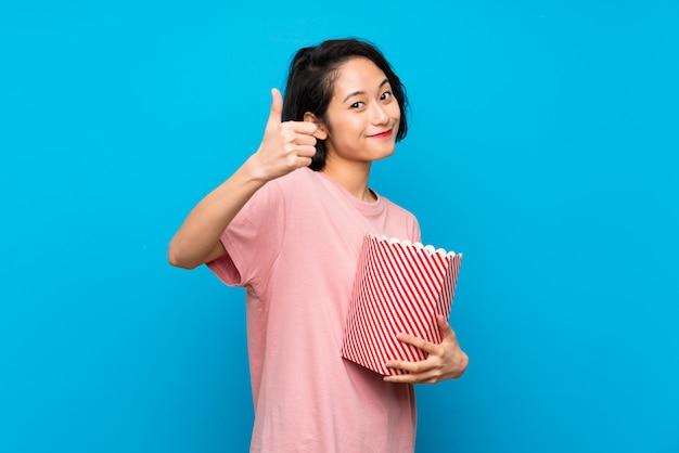 Asiatique jeune femme mangeant des popcorns avec le pouce levé parce qu'il s'est passé quelque chose de bien Photo Premium