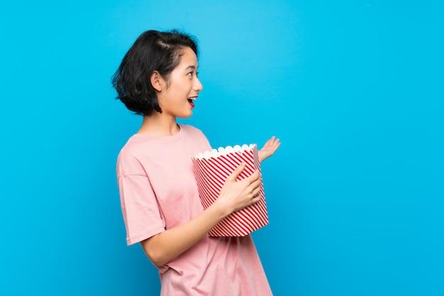 Asiatique, jeune femme, manger, pop-corn, surprise, expression faciale Photo Premium