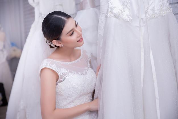 Asiatique jeune femme mariée essayant de robe de mariée au mariage moderne Photo gratuit
