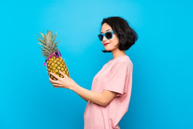 Asiatique jeune femme sur un mur bleu isolé, tenant un ananas avec des lunettes de soleil Photo Premium