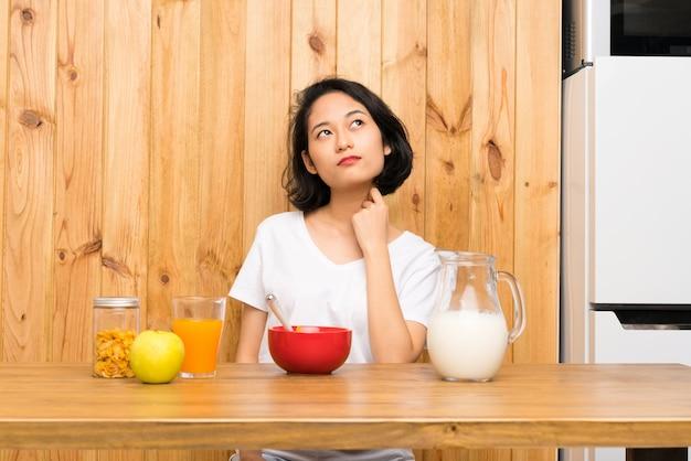 Asiatique jeune femme prenant son petit déjeuner lait pensant une idée Photo Premium
