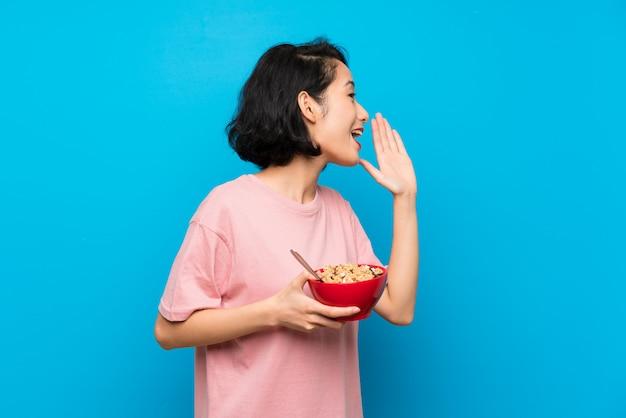 Asiatique jeune femme tenant un bol de céréales en criant avec la bouche grande ouverte Photo Premium