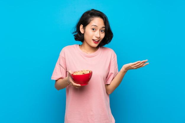 Asiatique jeune femme tenant un bol de céréales avec une expression faciale choquée Photo Premium