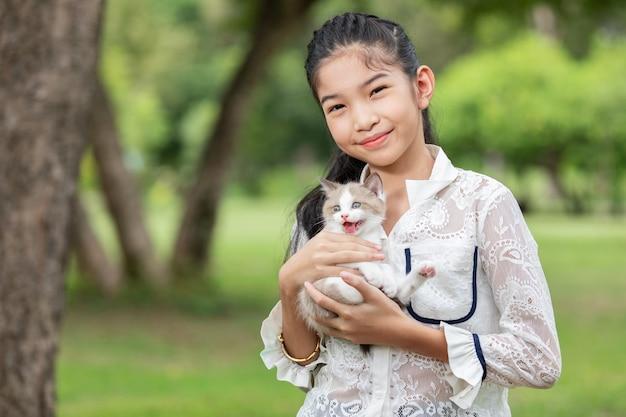 Asiatique Jeune Fille Tenant Des Chatons Dans Le Parc Photo gratuit