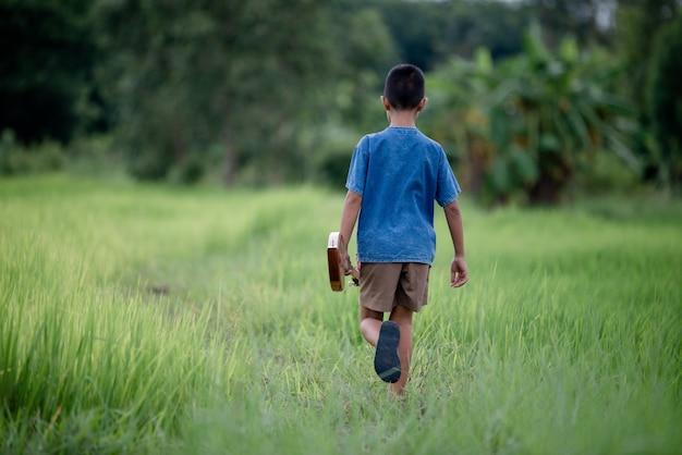 Asiatique jeune garçon avec guitare fait à la main en plein air, pays de la vie Photo gratuit
