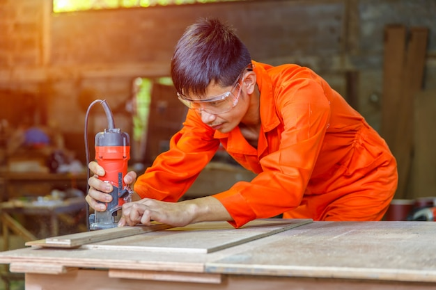 Asiatique jeune homme charpentier travaillant avec avion sur fond en bois Photo Premium