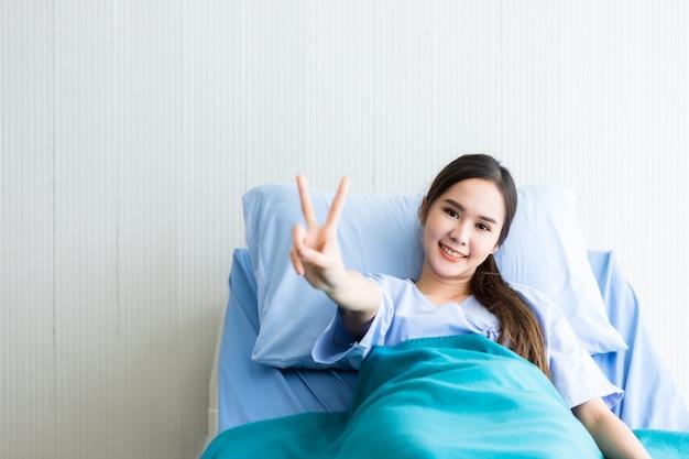 Asiatique jeune souriante patiente visage soulève deux doigts se battre avec la maladie sur lit dans la chambre hôpital Photo Premium