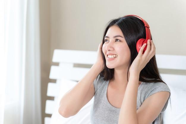 Asiatique jolie femme adolescente portant un casque bluetooth rouge, danse et smiley pour écouter de la musique avec joie Photo gratuit