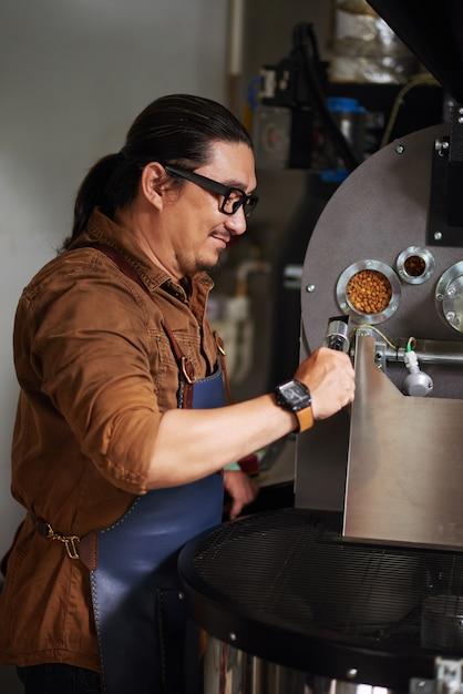 Asiatique mature en tablier debout à côté d'un équipement de torréfaction du café et de contrôle Photo gratuit
