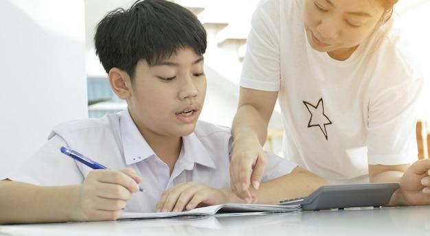 Asiatique mère aider son fils à faire leurs devoirs sur la table blanche. Photo Premium