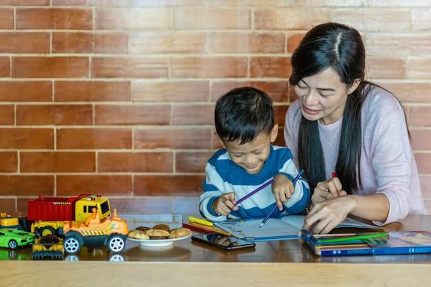 Asiatique mère célibataire avec son fils sont réunis dans loft house pour l'auto-apprentissage ou l'école à la maison Photo Premium