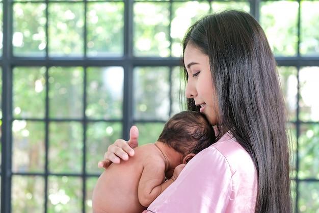 Asiatique mère tenant un nouveau-né, se penchant sur son épaule Photo Premium