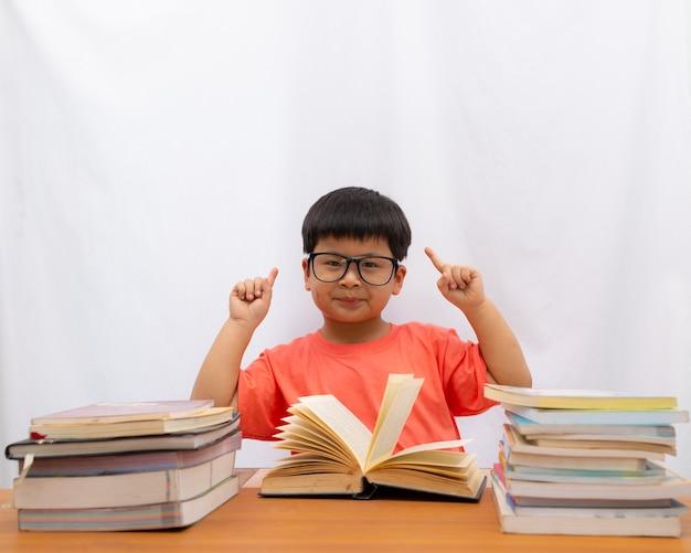 Asiatique mignon un petit garçon lisant avec un doigt tenant sur fond blanc, Photo Premium