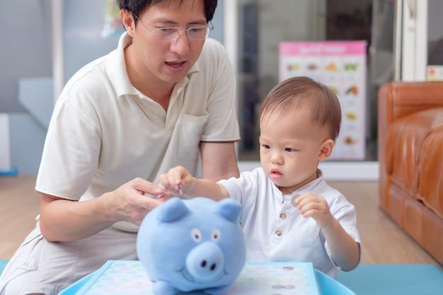 Asiatique père et enfant garçon mettant la pièce thaïlandaise dans la tirelire bleue Photo Premium