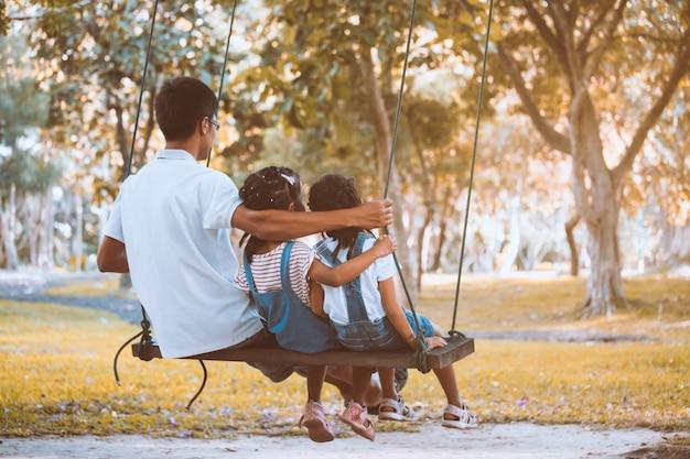 Asiatique père et fille s'amuser à monter sur des balançoires ensemble dans l'aire de jeux au parc Photo Premium