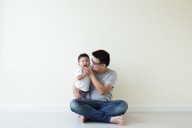 Asiatique père et fils jouant et souriant sur le sol dans la chambre Photo Premium