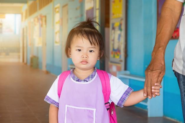 Asiatique petite écolière asiatique en uniforme et sac rouge va à l'école, retour à l'école. Photo Premium