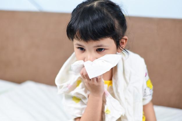 Asiatique petite fille malade, enveloppée dans un mouchoir, attrape froid et mouche du nez pendant la saison de la grippe, nez de l'enfant qui coule et éternuements se moucher et fièvre à la maison Photo Premium