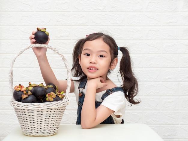 Asiatique petite fille mignonne et mangoustans (garcinia mangostana) dans le panier en bois sur fond blanc. Photo Premium