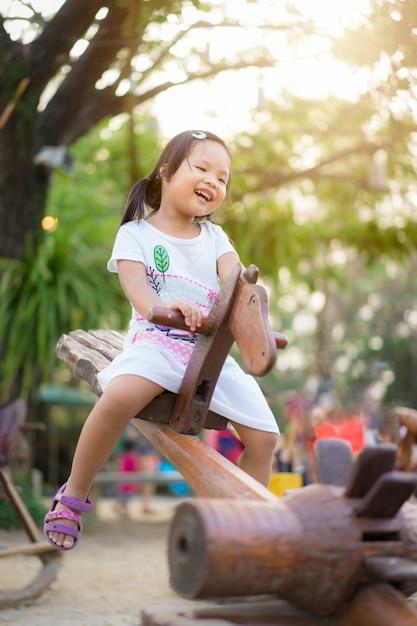 Asiatique petite fille s'amuser sur la bascule au terrain de jeux Photo Premium