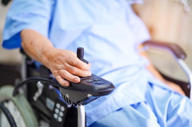 Asiatique senior ou âgée vieille dame patiente sur un fauteuil roulant électrique avec télécommande à l'hôpital de soins infirmiers. Photo Premium