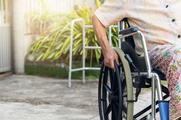 Asiatique senior ou âgée vieille dame patiente sur fauteuil roulant à la maison avant Photo Premium