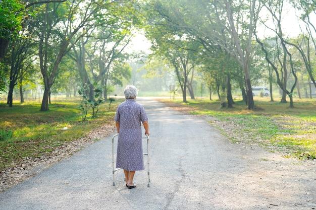 Asiatique senior ou âgée vieille dame patiente marche avec walker dans le parc Photo Premium
