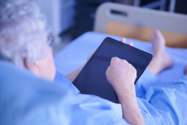 Asiatique senior ou âgée vieille dame patiente tenant dans sa tablette numérique de mains. Photo Premium