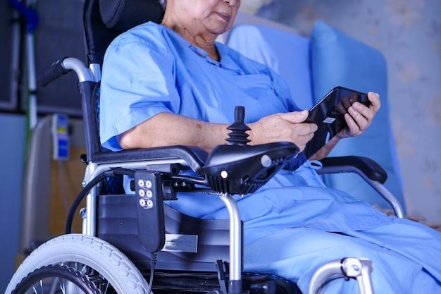Asiatique senior ou âgée vieille dame patiente tenant dans ses mains une tablette numérique et lire des emails tout en restant assise sur son lit dans un hôpital de soins infirmiers Photo Premium