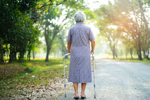 Asiatique senior ou âgée vieille dame vieille patiente marche avec walker dans le parc. Photo Premium