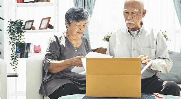 Asiatique senior homme et femme ouvre la boîte avec le visage souriant. Photo Premium